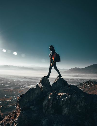 Man standing on rocky mountain against sky