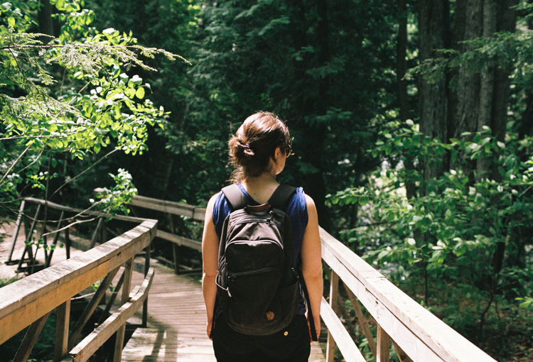 Rear view of woman standing on footbridge in forest