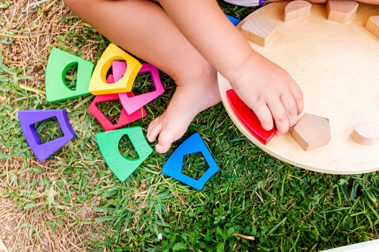Low section of woman playing with toy on grass