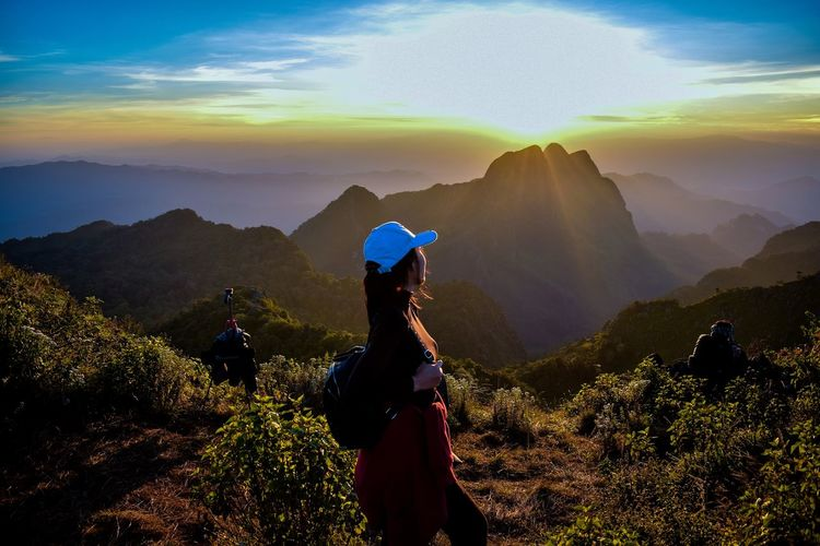 Female Hiker Standing On Mountain Against Sky During Sunset