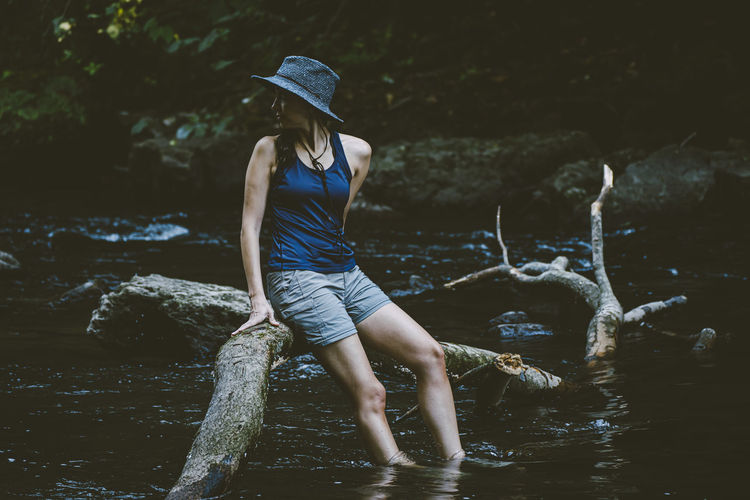 Woman standing on rock in water