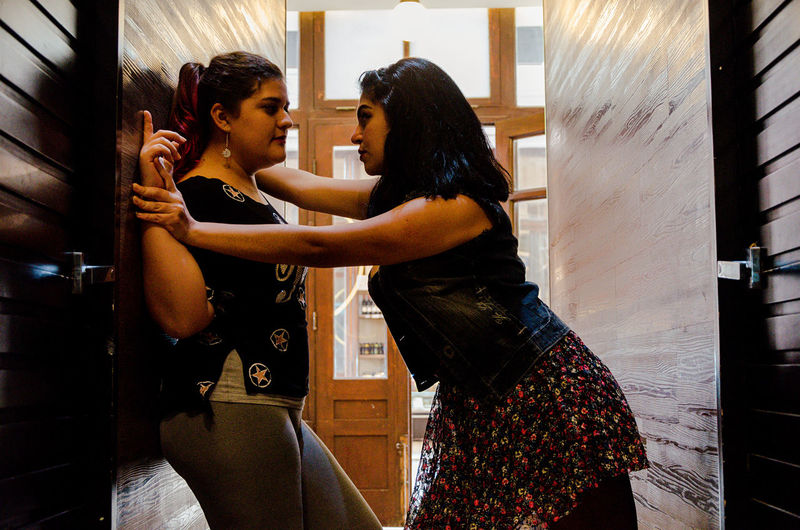 Side view of lesbian couple romancing in corridor