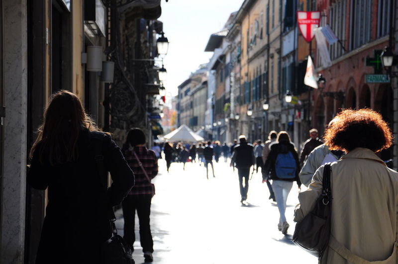 Pedestrians walking on city street amidst buildings in italy.
