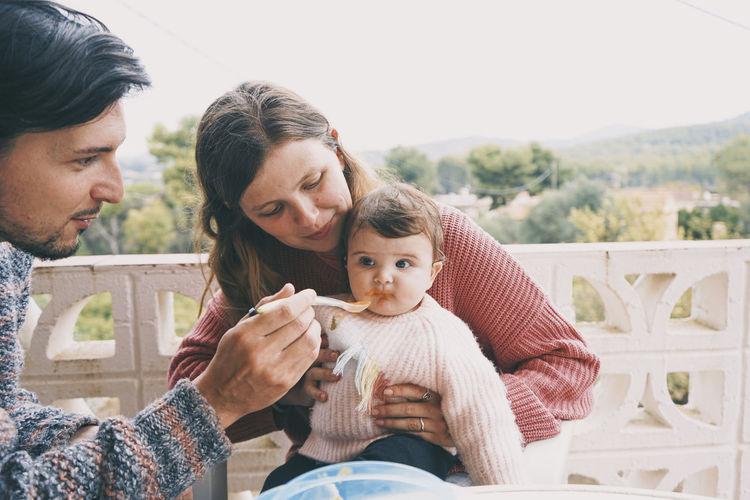 Couple feeding daughter in balcony