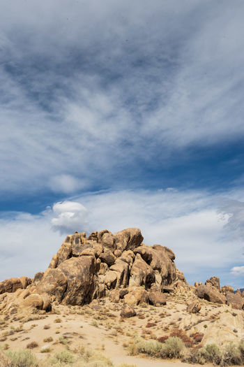Low angle view of rock formations against sky filled with cloud layers