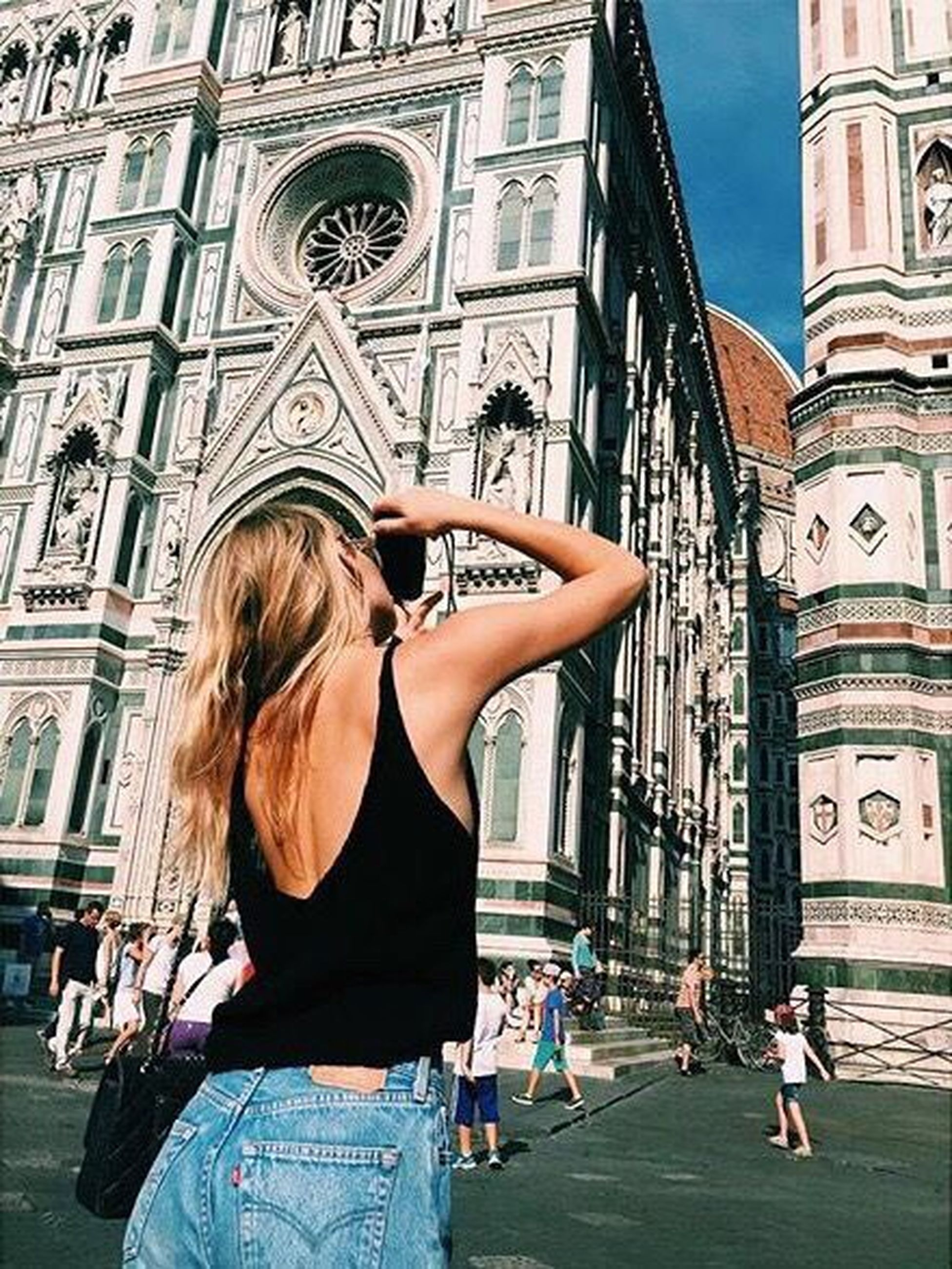 architecture, building exterior, built structure, lifestyles, leisure activity, famous place, person, tourism, city, capital cities, young adult, travel destinations, young women, tourist, international landmark, casual clothing, standing, travel