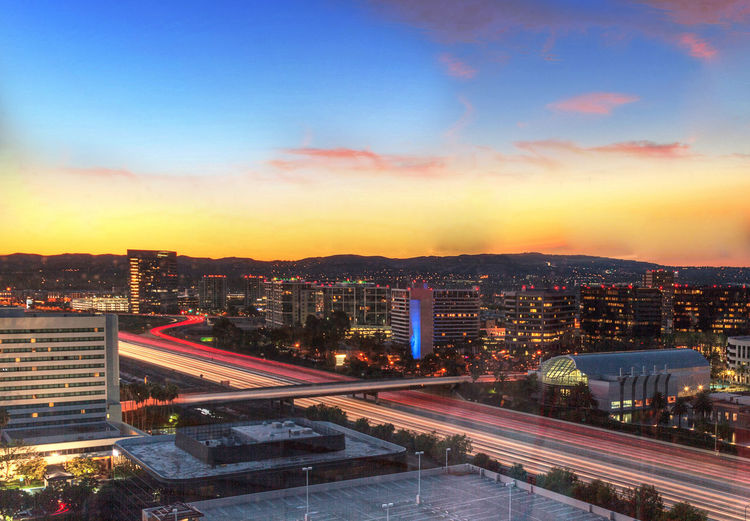 Sunrise over a highway in Irvine, California as headlight trails move through the roadways. Architecture Buildings Freeway Headlight Trails Headlights Headlights And Taillights Highway Irvine Irvine, California. Sky And Clouds Sunrise Transportation United States