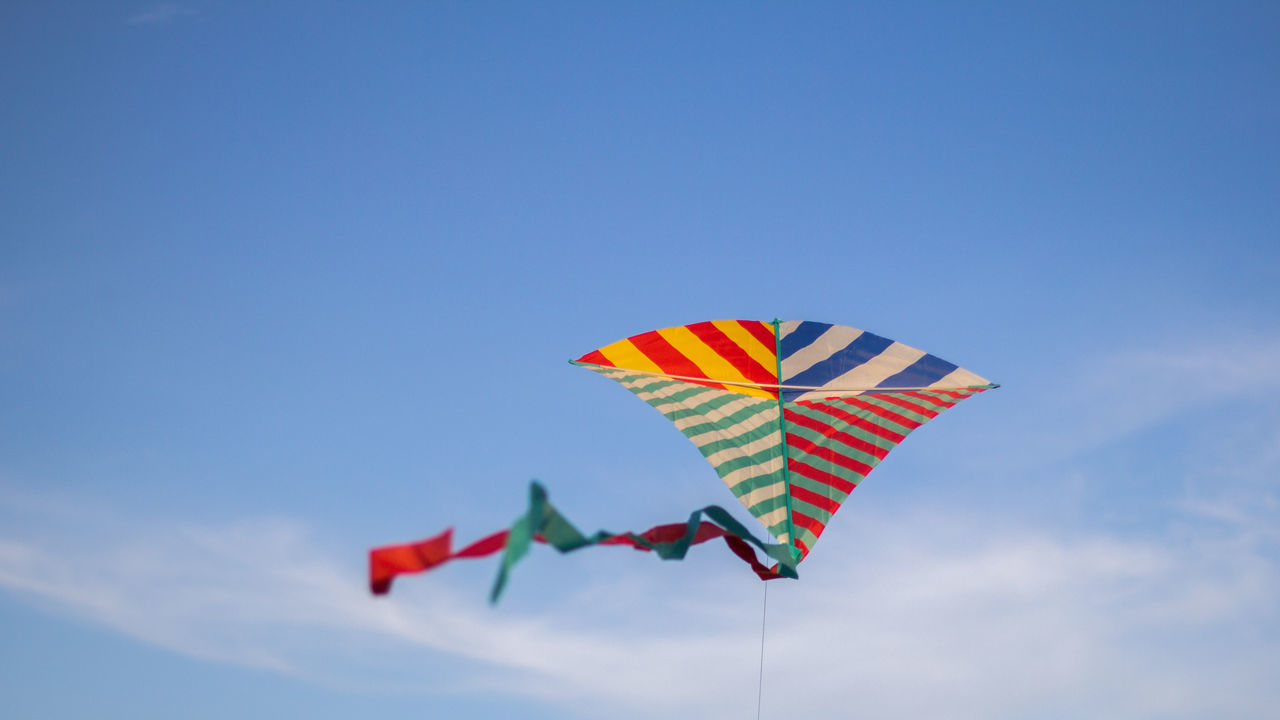 sky, multi colored, low angle view, cloud - sky, nature, flying, no people, blue, day, copy space, kite - toy, environment, mid-air, kite, striped, outdoors, wind, shape, motion