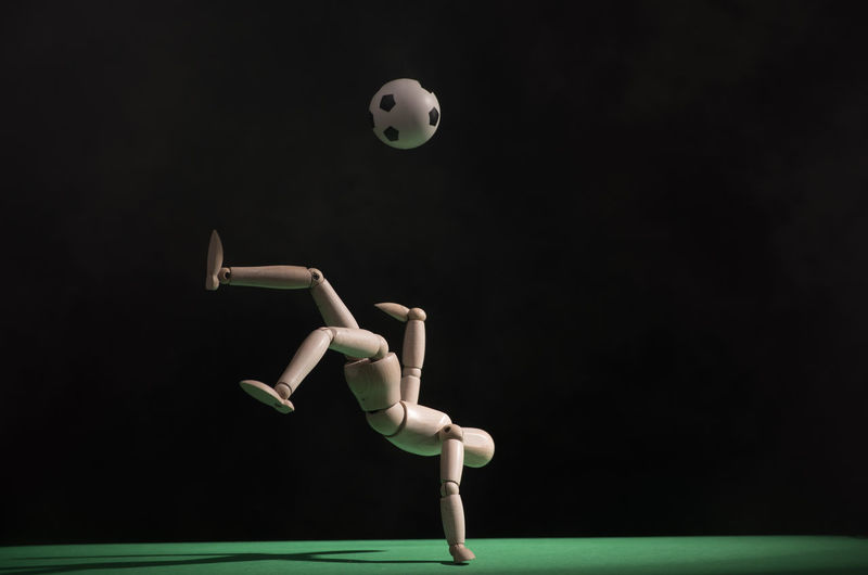 Close-up of figurine playing soccer against black background