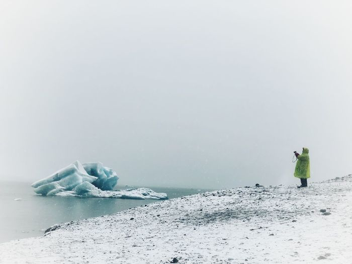 Person in sea against clear sky during winter