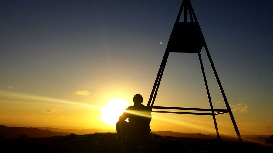Man Sitting By Tripod Against Sky During Sunset