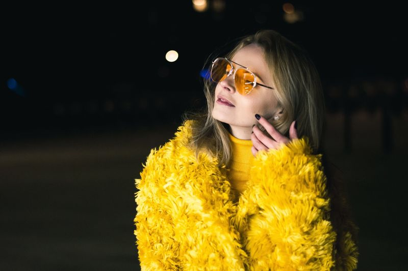 Close-Up Woman In Sunglasses And Yellow Dress At Night