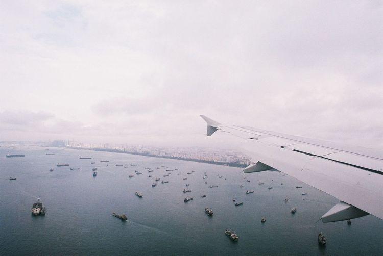 shot on film: flying over Singapore waters View From Above View From An Airplane Birds Eye View Ships Ships At Sea Ships On The Water Offshore Singapore Singapore View Singapore Sea Film Film Photography Filmisnotdead Airplane Flying Sea Water Air Vehicle Sky