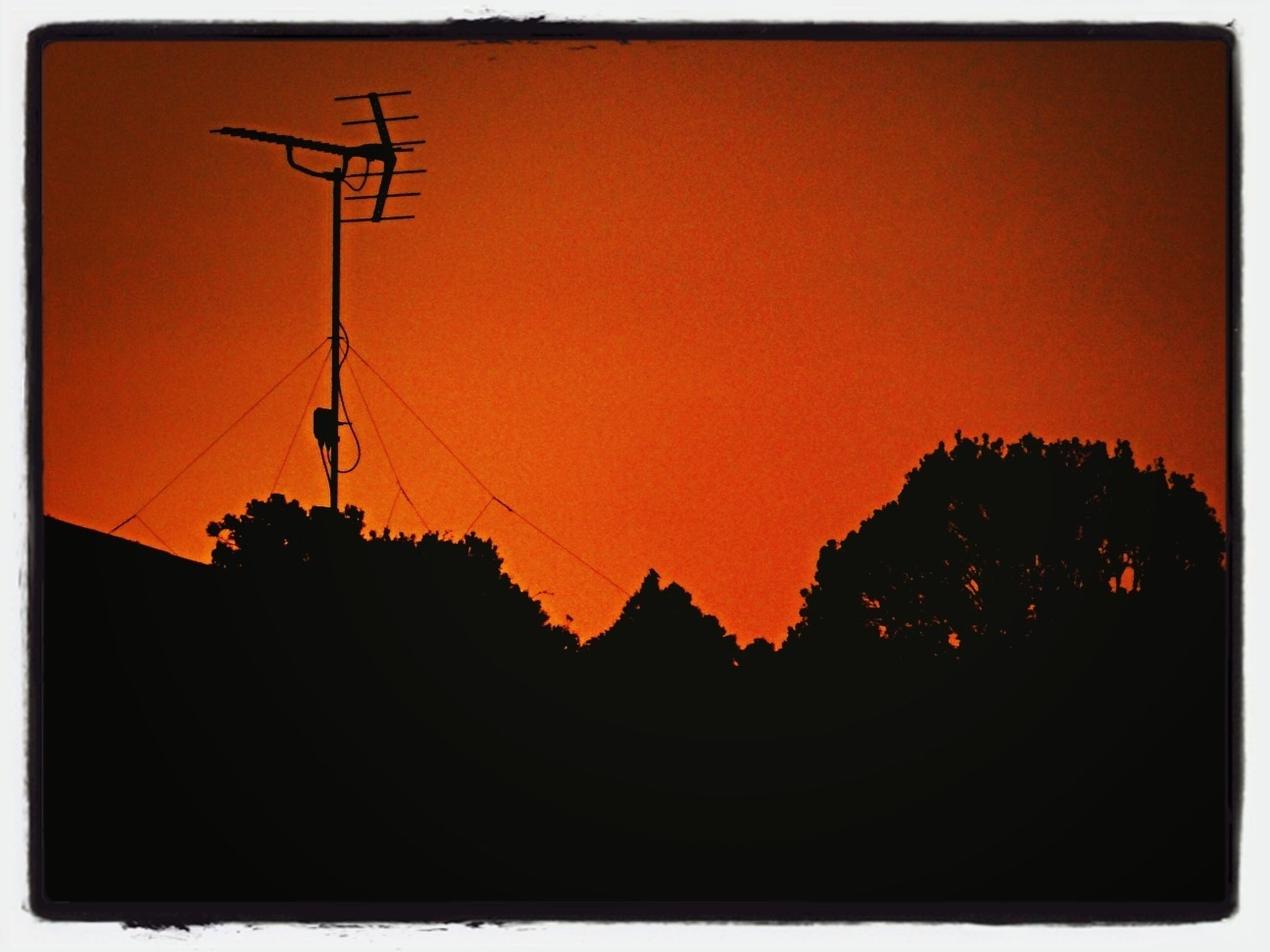 sunset, silhouette, transfer print, orange color, auto post production filter, copy space, sky, clear sky, building exterior, scenics, nature, built structure, beauty in nature, dusk, outdoors, tree, tranquility, architecture, power line, tranquil scene