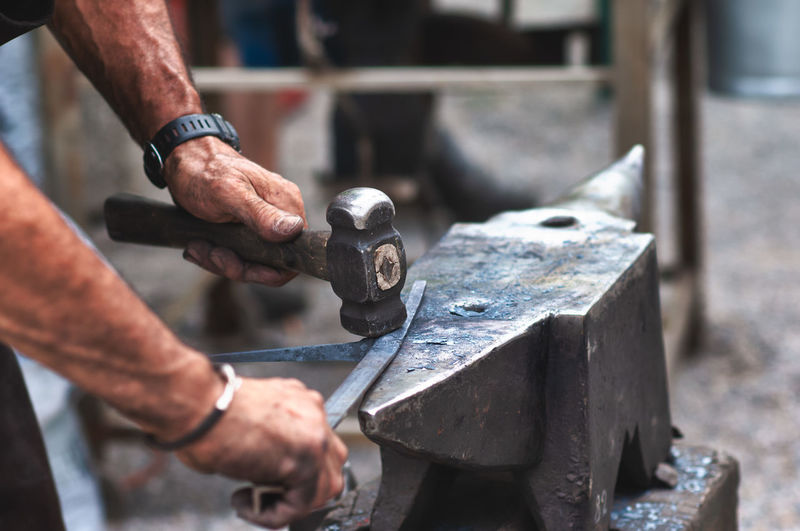 Cropped hands of blacksmith hammering metal on anvil