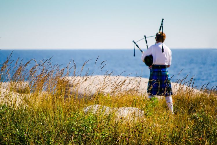Rear View Of Person Holding Bagpipe By Sea Against Sky