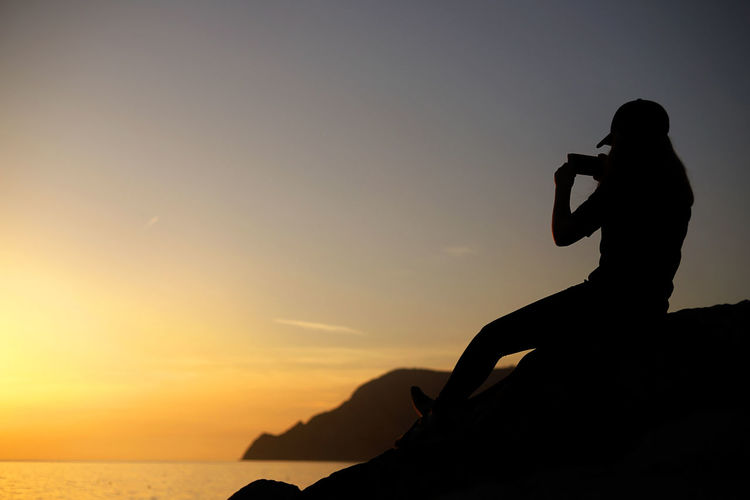 Silhouette woman photographing with mobile phone while sitting on rock against sky during sunset