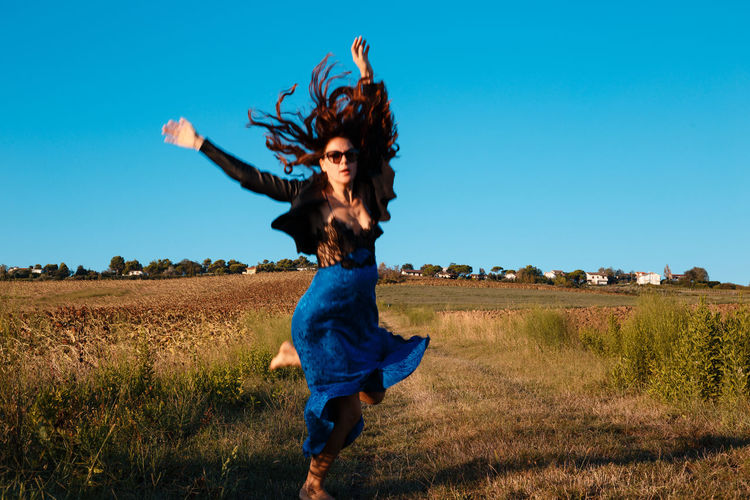 Full length of happy woman standing on field