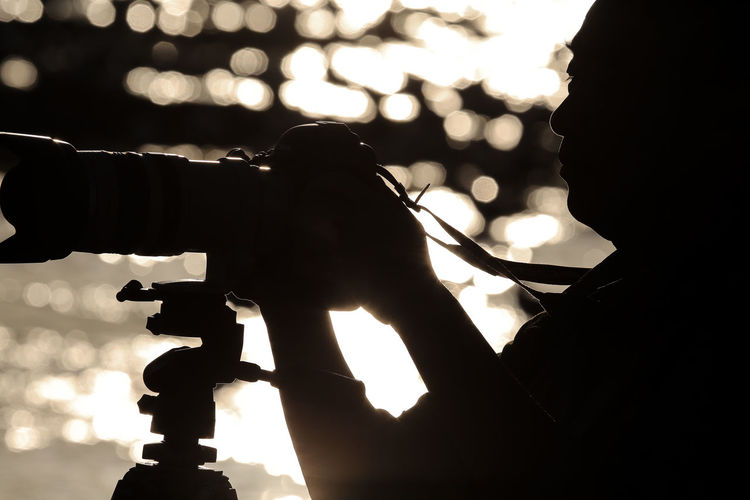 Close-up of silhouette man photographing with camera