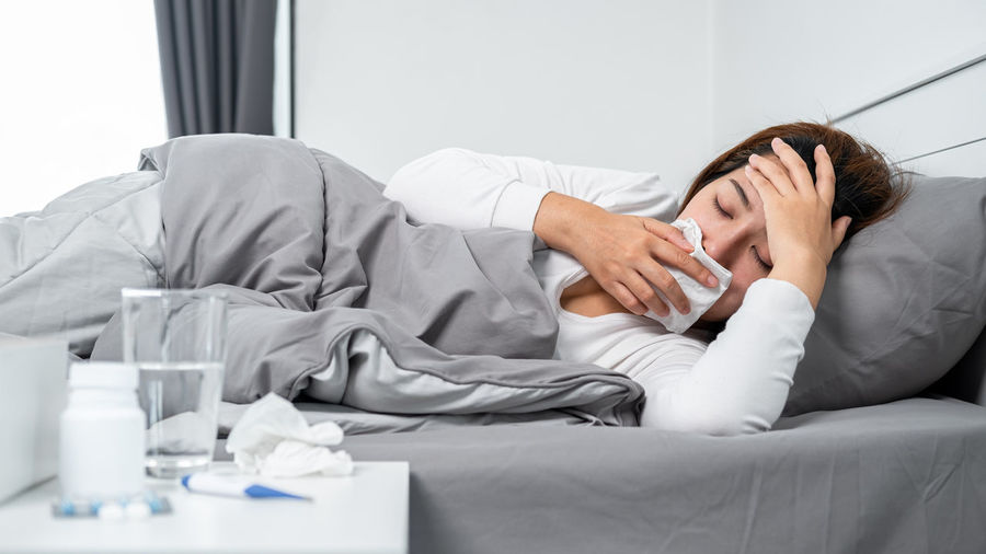 Midsection of man sleeping on bed