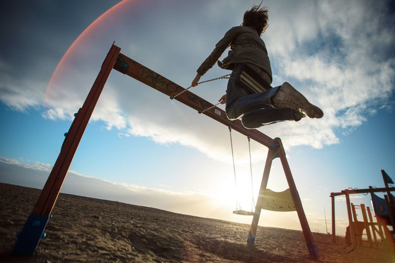 Low angle view of woman swinging on field
