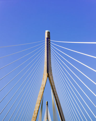 A cable stayed bridge Cable Stayed Bridge Cement Color Day Engineering Low Angle View Pylon Suspended vanishing point Bridge Length High Steel Blue Suspension Bridge Sky LINE Steel Cable
