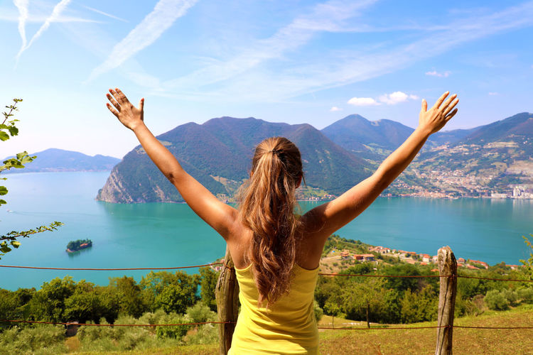 Rear view of woman looking at lake by mountains