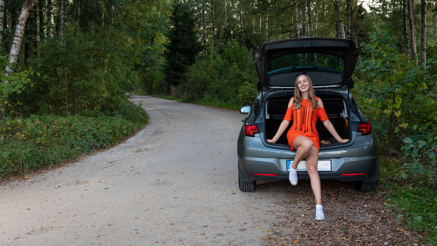 Portrait of smiling young woman sitting on car trunk against trees in forest