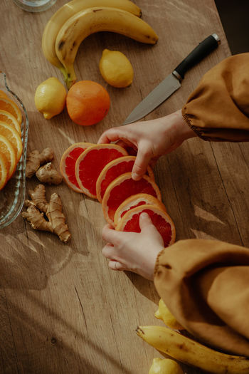 High angle view of person preparing fruits on cutting board
