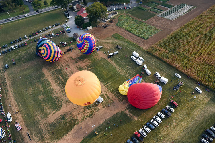 Up and away. Transportation High Angle View Mode Of Transport In A Row Outdoors Travel Destinations Land Vehicle Hot Air Balloons Lancaster County Pennsylvania Lancasterpa Hot Air Balloon Non-urban Scene Cars Balloons Grass Field Flight Runridesoar2016 Photography Tranquil Scene Scenic Tent Fair Tent Event