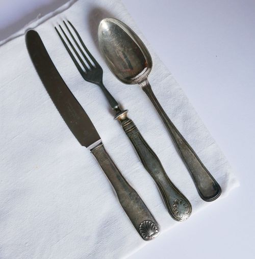 Close-up of fork with spoon and knife on table