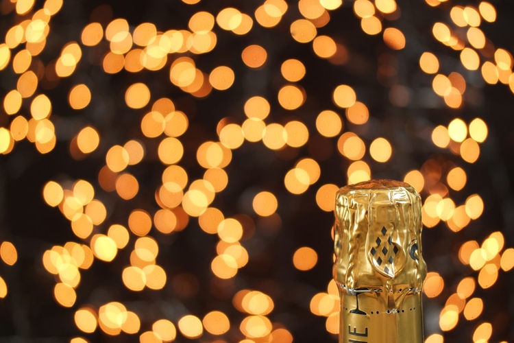 Close-up of champagne bottle against lights at night