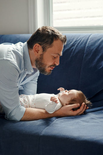 Proud caucasian father talking to newborn baby girl. smiling happy parent man calming down child