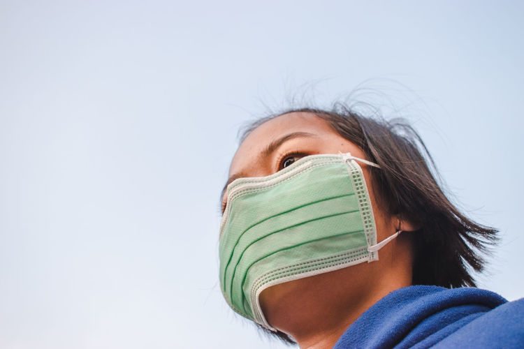Close-up of girl wearing pollution mask against sky