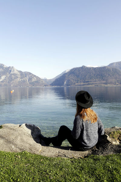 Beauty In Nature Day Hairstyle Hat Lake Leisure Activity Lifestyles Looking At View Mountain Mountain Range Nature One Person Outdoors Real People Rear View Relaxation Scenics - Nature Sitting Sky Tranquil Scene Tranquility Water Women