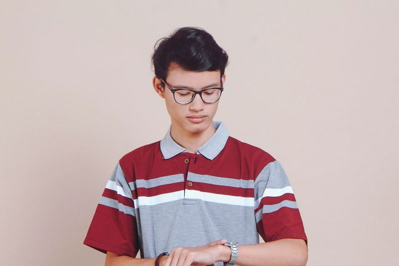 Young Man Checking Time While Standing Against Brown Background