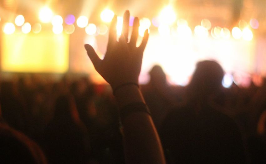 Close-up of hand raised at music concert