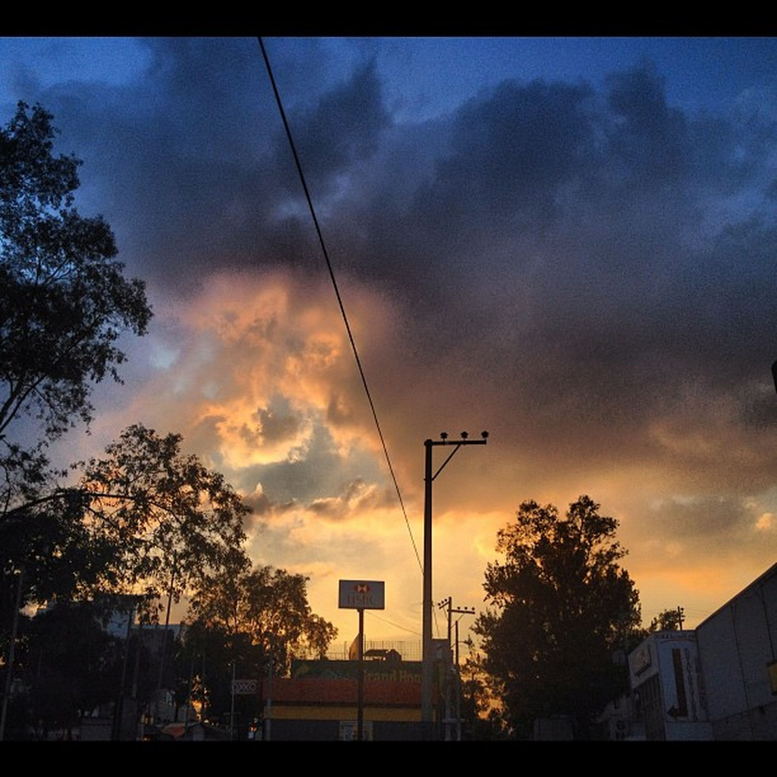 sky, silhouette, tree, power line, sunset, cloud - sky, low angle view, building exterior, built structure, architecture, electricity pylon, cloudy, electricity, power supply, cable, cloud, fuel and power generation, house, dusk, connection