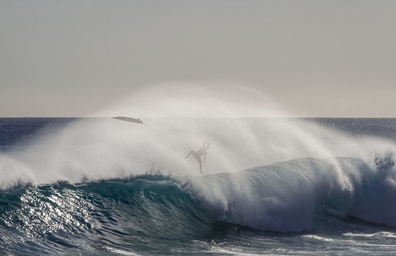A Surfer falling into a big wave Falling Hawaii Man Oahu Surf Wave Aquatic Sport Day Horizon Over Water Motion Nature Outdoors Power Power In Nature Recreational Pursuit Scenics - Nature Sea Sky Splashing Sport Spray Surfing Water Waterfront Wave