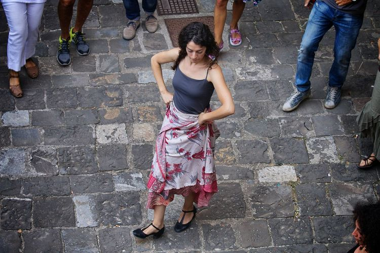 High angle view of woman dancing on footpath in city