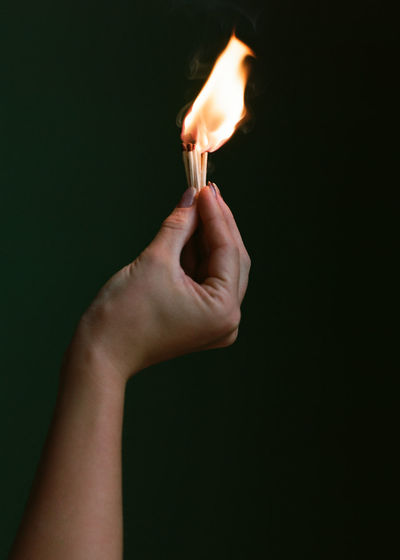 Close-up of hand holding burning matchsticks against black background