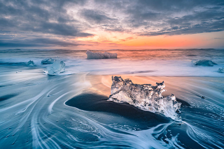 Ice at beach against sky during sunset