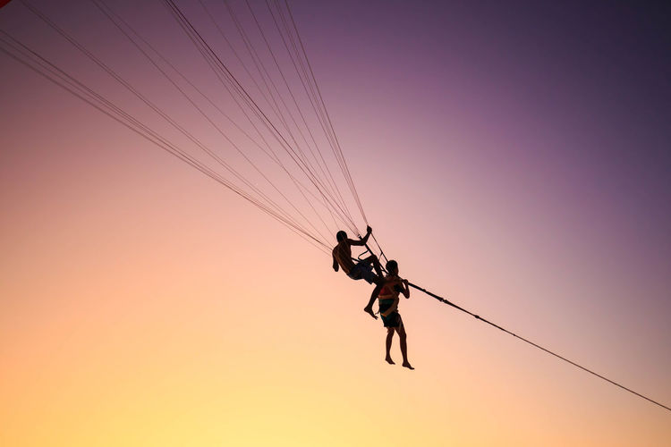 Low angle view of man parasailing against sky during sunset