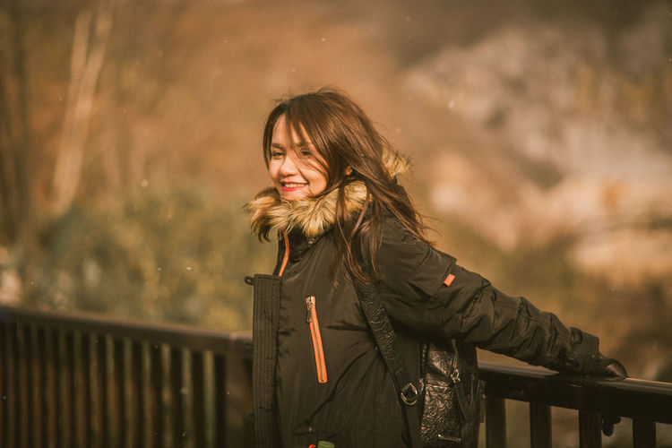 Portrait of smiling young woman standing against railing during winter