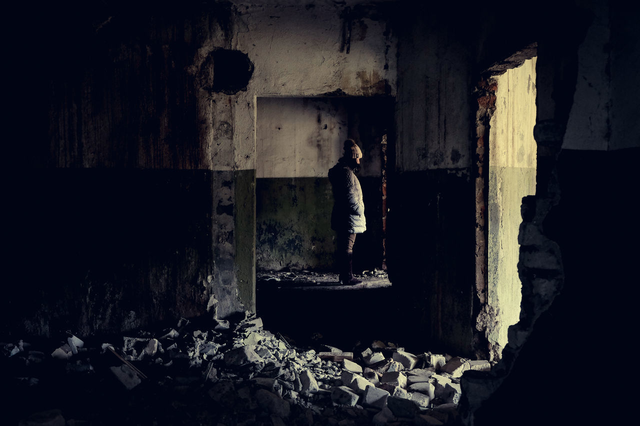 Side View Of Woman Standing At Abandoned Building