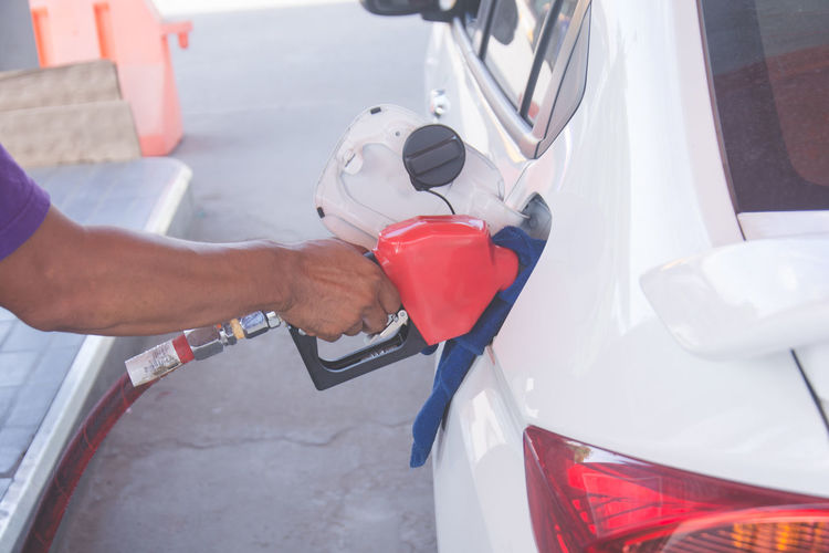 Cropped hand of man refueling car