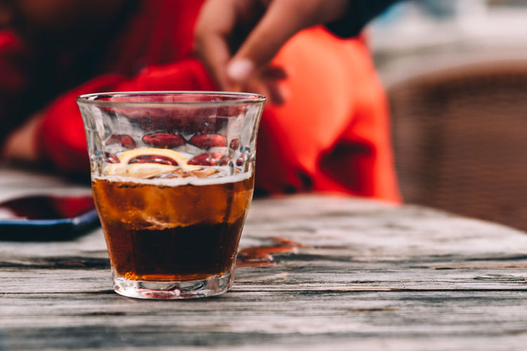 Glass of cola on wooden table at bar