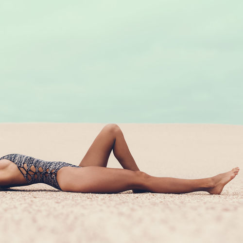 Glamorous tanned lady in a fashionable swimsuit at the beach