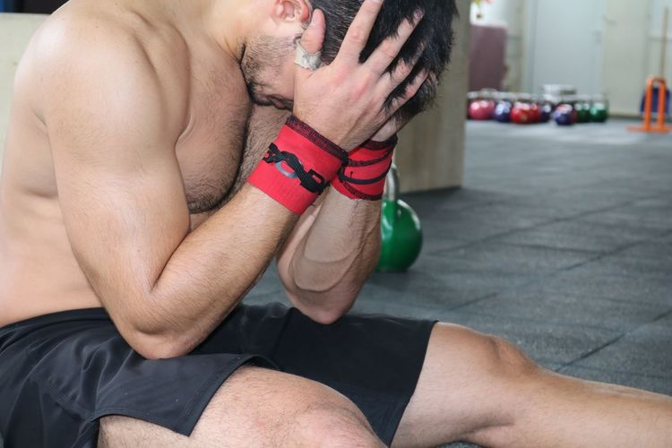 Tired muscular man relaxing in gym