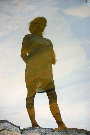 Mid adult woman standing against sky reflecting on calm lake